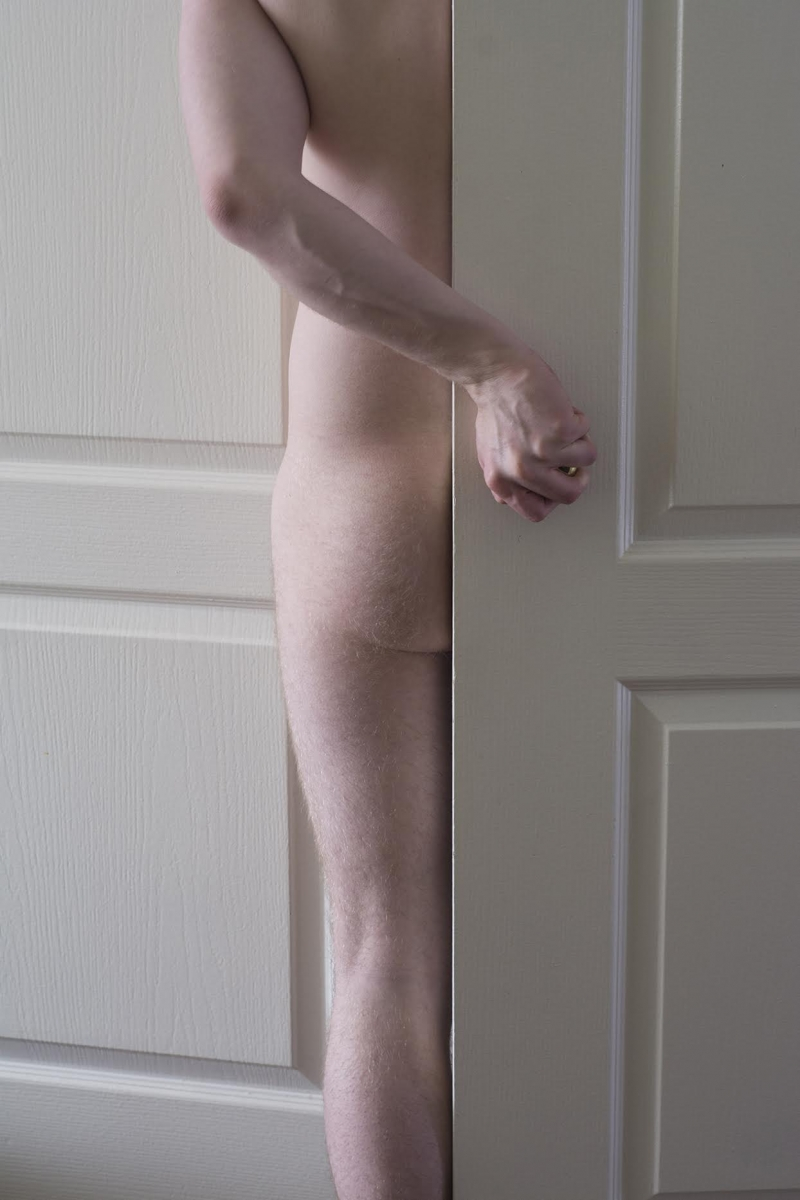 Nude male stands half obscured by door