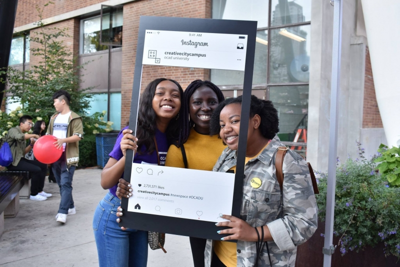 Three young women smiling and holding up a frame to look like Instagram
