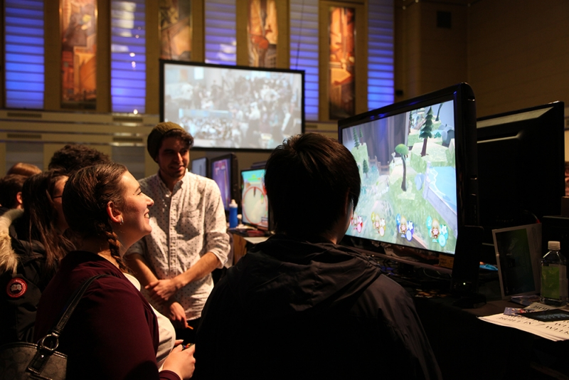 Three people looking at video game monitor