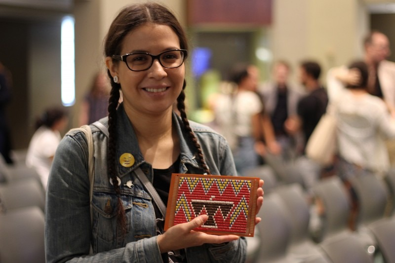 Karalyn Reuben - holds up a small square beaded thunderbird panel