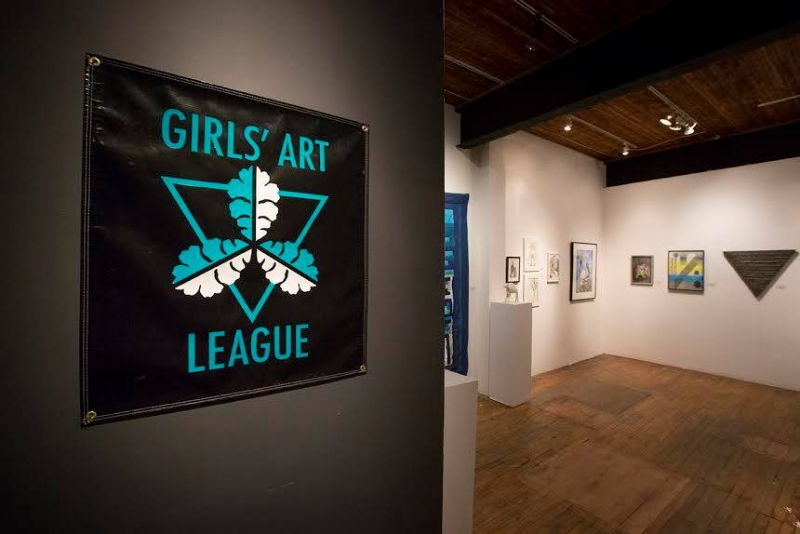 Photo of art gallery with Girls' Art League poster on wall