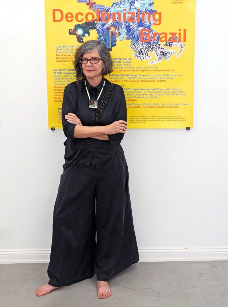 photo of Maria Thereza Alves in front of a yellow poster