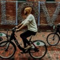 "cyclists use Bike Share Toronto across a mural reading the word ""LOVE"""