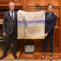 Two men holding up a large silk scarf depicting a man looking at the ocean